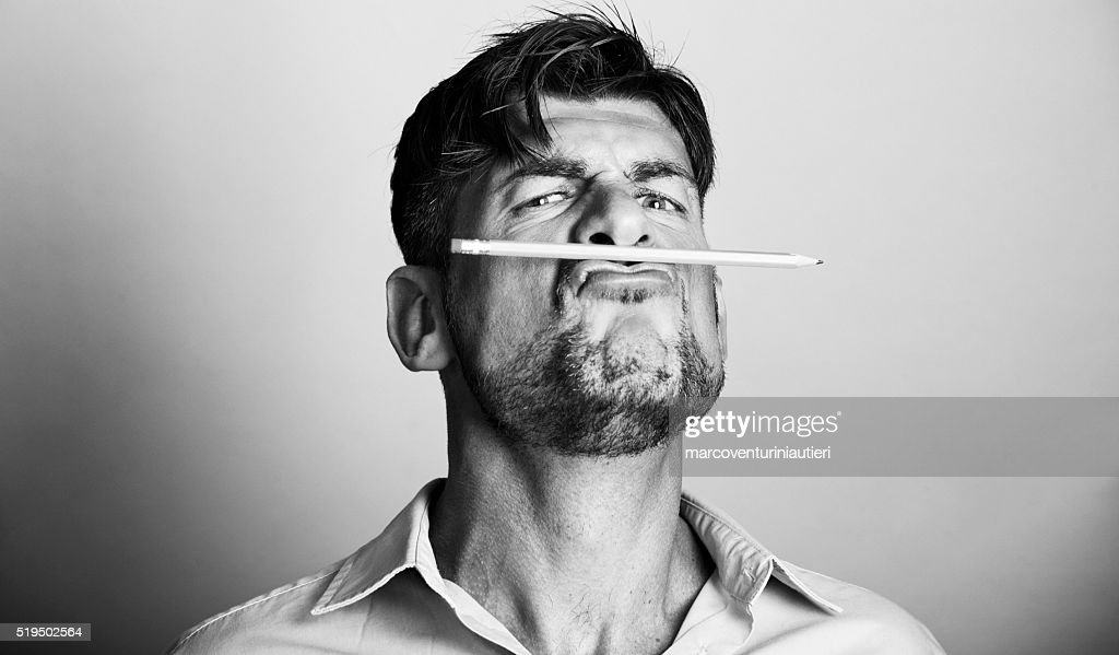 Mad artist holds a pencil with his lips : Stock Photo