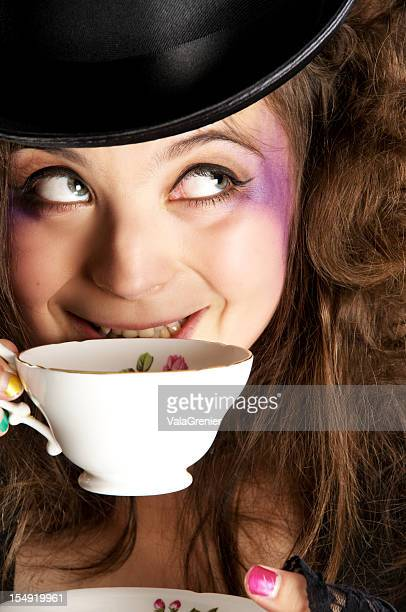 Mad hatter girl smiles about to drink tea.