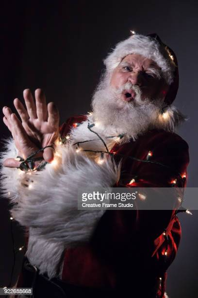mad santa claus tied up / tangled in christmas lights - pere noel libre de droit photos et images de collection