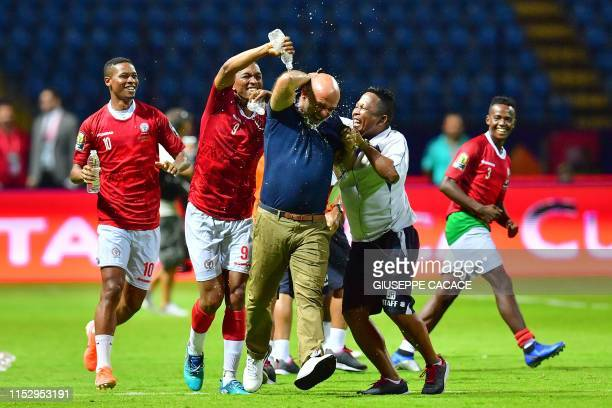 Madagascar's forward Faneva Andriatsima pours water on Madagascar's coach Nicolas Dupuis as they celebrate winning the 2019 Africa Cup of Nations...
