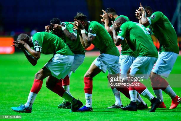 TOPSHOT Madagascar's players celebrate their goal during the 2019 Africa Cup of Nations football match between Guinea and Madagascar at Alexandria...