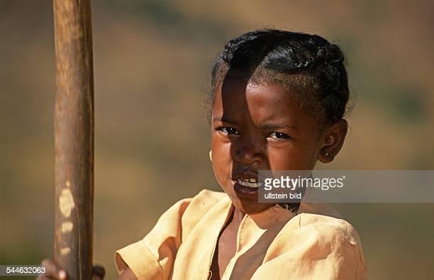 Mädchen mit einem Stößel zum Zerstampfen von Getreide