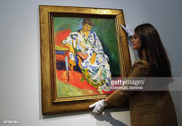'Madame Matisse au kimono' by Andre Derain is handled by a Christie's employee during a preview of Christie's Impressionist and Modern Art sales in...