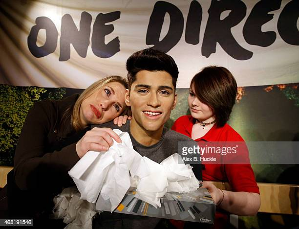 Madame Tussauds attendant hands One Direction fan Laura Tokely a tissue following the news of the departure of Zayn Malik from One Direction on March...