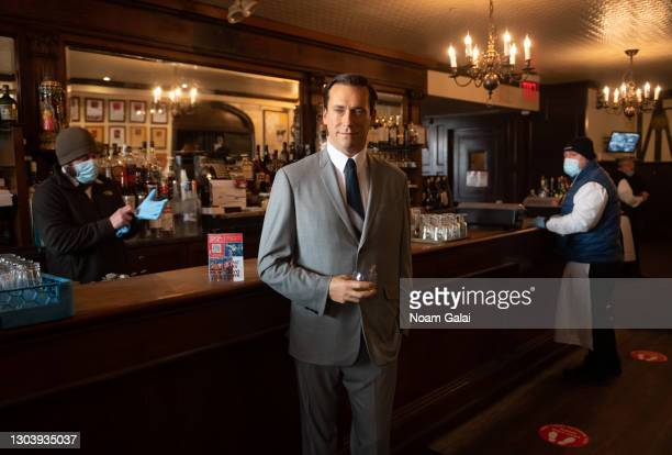 Madame Tussauds Jon Hamm wax figure holds a glass of whiskey by the bar at Peter Luger Steak House to help with social distancing amid the...