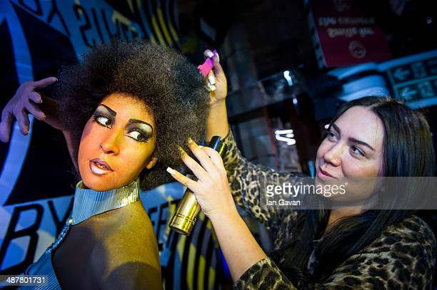 Madame Tussauds London Studio Artist Gemma Sim styles the hair of a wax model of Marsha Hunt in an iconic swinging sixties scene as part of regular...