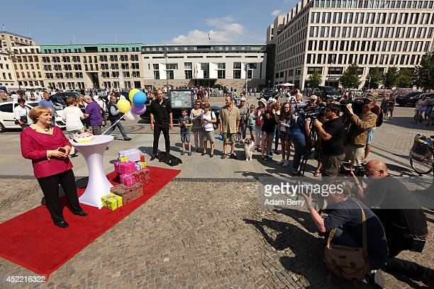 Madame Tussauds wax figure of German Chancellor Angela Merkel stands next to a birthday cake in front of the Brandenburg Gate on July 16 2014 in...