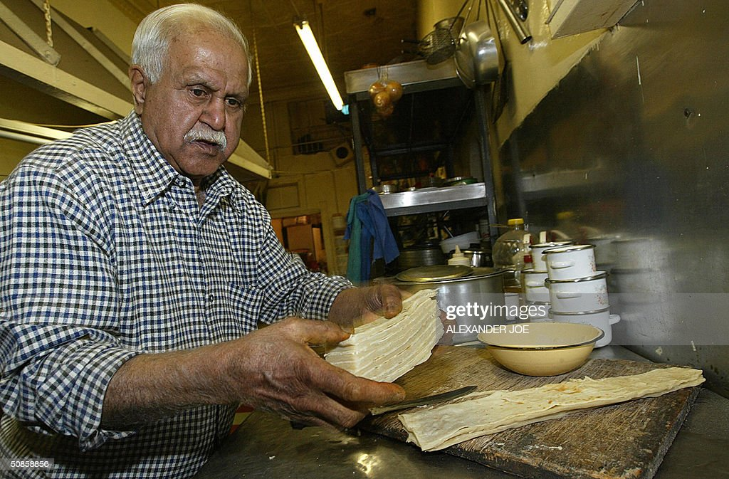 Madanjit Ranchod's the owner of Johannesburg's Historic Indian restaurant Kapitan's that was founded in 1887 his great-grandfather prepares some food, 19 May 2004. Kapitan's was Nelson Mandela daily lunch place in the 1950's as a young lawyer. Now Johannesburg's oldest Indian restaurant is struggling to survive, located deep in the heart of the city's now seedy central business. Ranchod now keeps the restaurant open only for lunch and only for 25 people daily. He cooks himself and claims the fare is unsurpassed.'I'm growing old and it's difficult to keep up, so I'm closed in the evening. If there are more than 25 people, you pay double. You also give me a good tip and if you are a rich man, I expect you to buy me a 500-rand (74-dollar / 62-euro) Cuban cigar,'. AFP PHOTO/ALEXANDER JOE