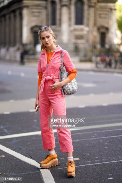 Maddie Close wears a pink corduroy jumpsuit, a knitted belt, a silver metallic bag, brown platform shoes, an orange top, sunglasses over the head, a...