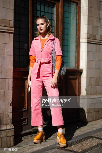 Maddie Close wears a pink corduroy jumpsuit, a knitted belt, a silver metallic bag, an orange top, sunglasses over the head, a ring, brown platform...