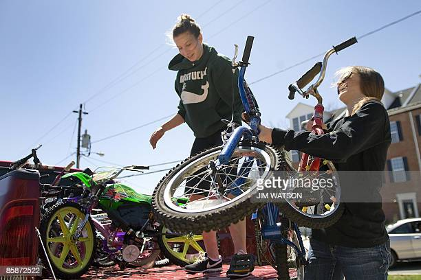 Maddie Myer and Heather Cromartie unload donated bicycles froma pickup truck as they volunteer during a bicycle collection drive on April 4 2009 for...