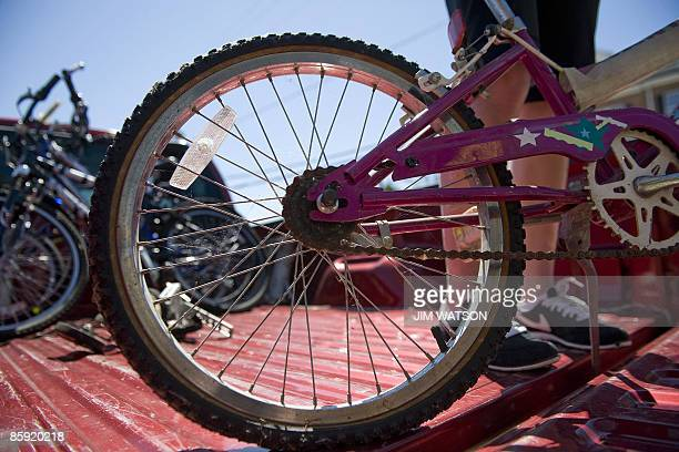 Maddie Myer helps unload bicycles from the back of a pickup truck as she volunteers during a bicycle collection drive on April 4 2009 for 'Bikes for...