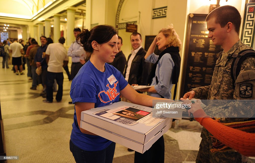 Maddie Potter, 20, a student at The University of Pittsburgh, passes out pizza as voters stand in line to cast a ballot during evening voting at a polling station on Election Day on November 4, 2008 in Pittsburgh, Pennsylvania. After nearly two years of presidential campaigning, U.S. citizens go to the polls tonight to vote in the election between Democratic presidential nominee U.S. Sen. Barack Obama (D-IL) and Republican nominee U.S. Sen. John McCain (R-AZ).