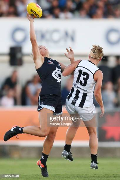 Maddison Gay of the Blues juggles a one handed mark against Jamiee Lambert of the Magpies during the round one AFLW match between the Carlton Blues...