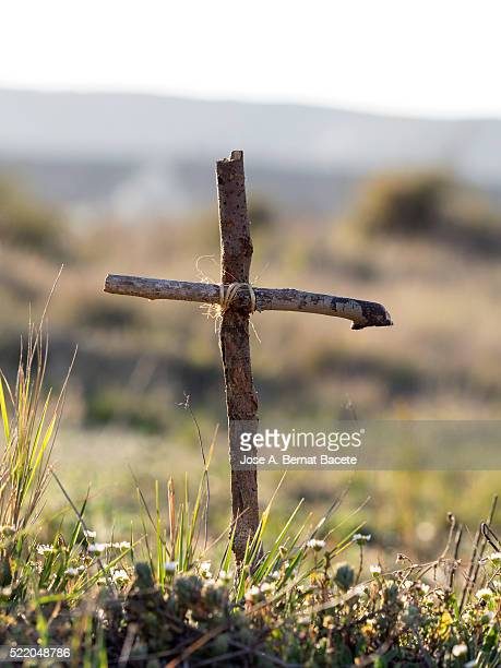 made cross of sticks of wood of a tomb in the field, on a clear sky - crosses with flowers stock pictures, royalty-free photos & images