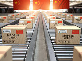 Made in China. Cardboard boxes with text made in China and chinese flag on the roller conveyor.