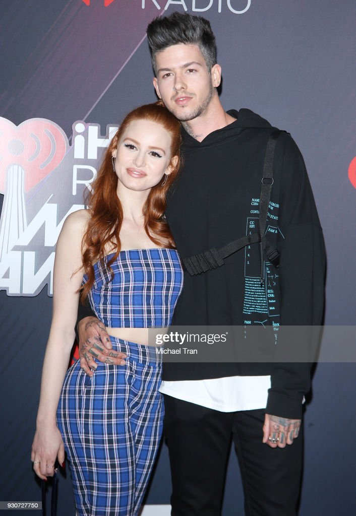 Madelaine Petsch (L) and Travis Mills arrive to the 2018 iHeartRadio Music Awards held at The Forum on March 11, 2018 in Inglewood, California.