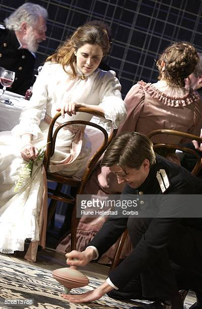 """Madeleine Worrall watches an actor spin a large top in a scene from the new production of Chekhov's """"Three Sisters"""" at the Playhouse Theatre."""
