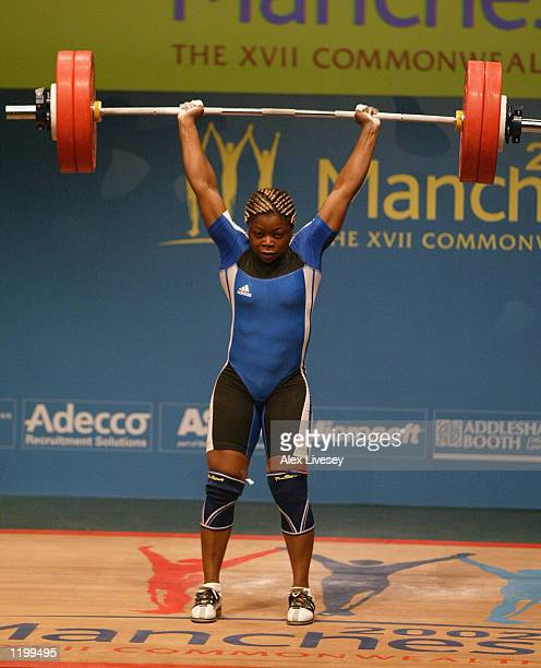 Madeleine Yamechi of Cameroon celebrates with her coach after winning Gold for the Clean and Jerk in the women's upto 69kgs Weightlifting competition...