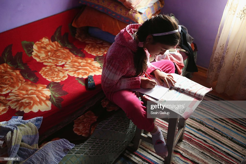 Madelina, 10, an ethnic Roma, does her English homework in the living room of her grandparents house where she lives on March 11, 2013 in Dilga, Romania. Madelina's mother, as well as both of her uncles, live and work in Italy, send money to their parents and only come to Dilga once a year to visit. Dilga is a settlement of 2,500 people with dirt roads and no running water, and unemployment is at 70%. Most of the working-age men and women have at some point worked abroad, mostly in Italy or Great Britain, as many say they are unable to find adequate work in Romania. Romania's Roma belong to a myriad of different tribes defined by their craft, and Dilga's belong to a group called the Rudari, who until the 1930s specialised in woodcrafts. During the communist years most worked in nearby state-run factories and agricultural cooperatives, though the majority of these went bankrupt after 1989 and the local Roma lost their jobs. Since then they have struggled to make ends meet and find a better future for their children, though projects initiated by the European Union and NGOs are helping some to launch small-scale enterprises and improve their children's education.