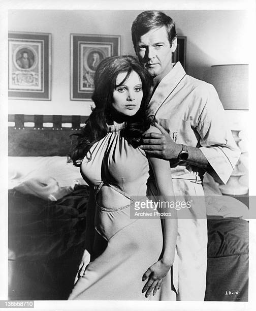 Madeline Smith leaning against Roger Moore in a suggestive manner as he touches her arm in a scene from the film 'Live And Let Die' 1973