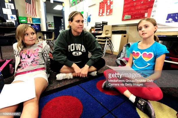 Madeline Smith, left and teacher Jennifer Rosenfels, listen to Kalani Gilman read out her list of positive body image words during a Girls on the Run...
