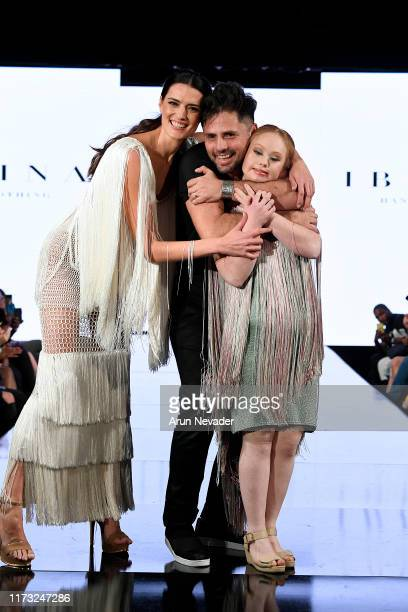 Madeline Stuart walks the runway with a designer and model during IBRAINA At New York Fashion Week Powered by Art Hearts Fashion NYFW September 2019...