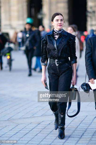 Madelynn Furlong wears a black and white striped turtleneck top, a black ruffled jacket, a leather belt with metallic buckle, black denim pants,...