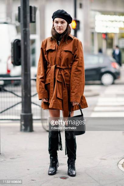 Madelynn Furlong wears a black beret hat, a black turtleneck, a brown trench coat, a black Prada bucket handbag, black knee-high boots with braided...