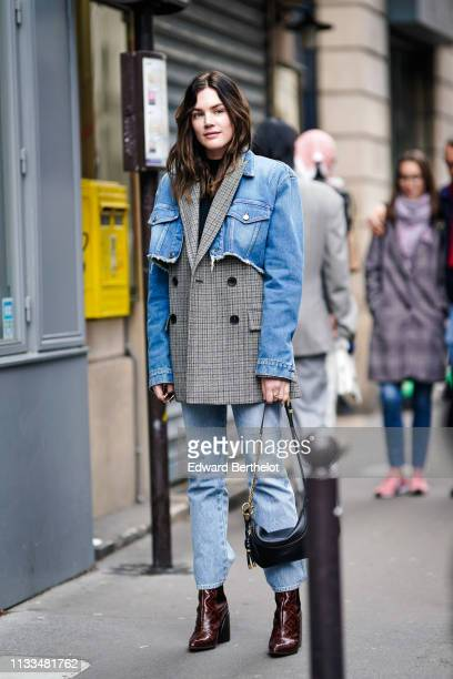 Madelynn Furlong wears a blue denim ripped jacket ver a checked blazer jacket, blue jeans, a black leather fanny pack bag, burgundy shoes, outside...