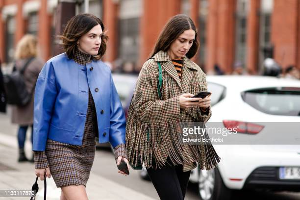 Madelynn Furlong wears a turtleneck brown and blue tweed dress a lavenderblue leather jacket Erika Boldrin wears an orange and black striped top a...