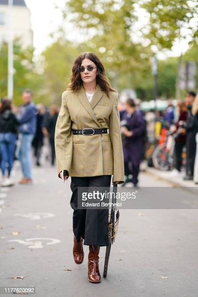 Madelynn Furlong wears an oversized blazer jacket, a belt, cropped flared pants, brown leather boots, sunglasses, outside Nina Ricci, during Paris...