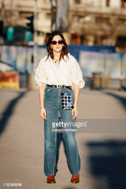Madelynn Furlong wears sunglasses a white shirt a leather belt a bag with shiny sequin blue denim flared pants brown shoes outside Koche during Paris...