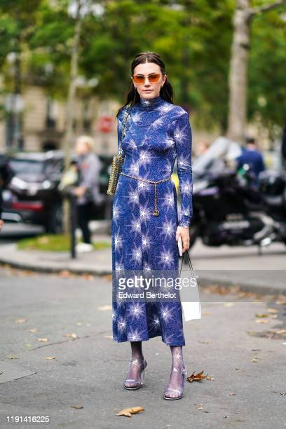 Madelynn Furlong wears sunglasses, earrings, a hi-neck blue dress with sparkling white stars print midi dress, a gold metal mesh bag, a Gucci chain...