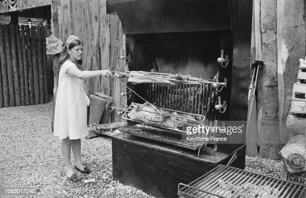 Mademoiselle Katherine Tewe élue 'Reine des Loges 1967' arrosant un morceau de mouton cuisant devant une rotisserie à SaintGermainenLaye France le 20...