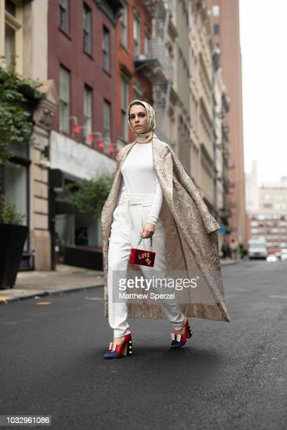 Mademoiselle Meme is seen on the street attending New York Fashion Week SS19 wearing long silver coat with white outfit and red 'Love Me' bag with...