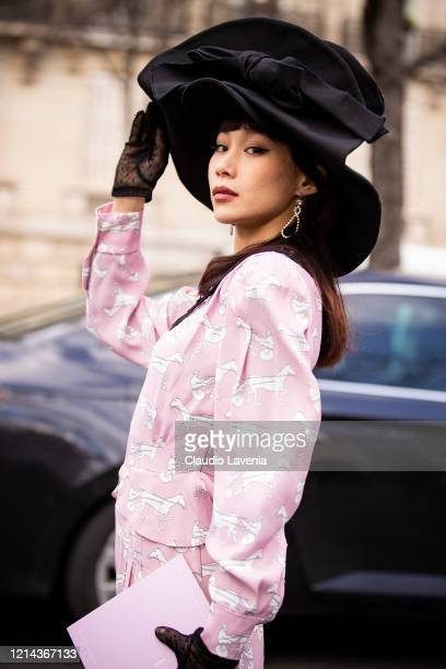 Mademoiselle Yulia wearing a pink printed jacket black seethrough gloves and black hat is seen outside Miu Miu during Paris Fashion Week Womenswear...