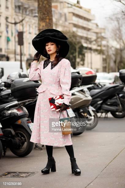 Mademoiselle Yulia wearing Miu Miu black oversized velvet hat dress and straw clutch outside the Miu Miu show during Paris Fashion Week Womenswear...