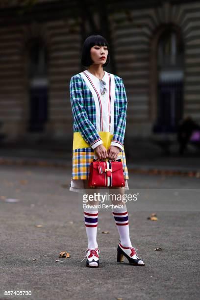 Mademoiselle Yulia wears a checkered blazer jacket a red bag socks outside Thom Browne during Paris Fashion Week Womenswear Spring/Summer 2018 on...