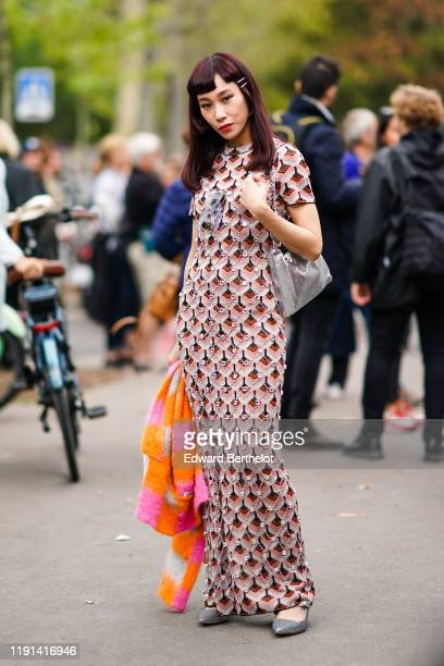 Mademoiselle Yulia wears a dress with printed geometric patterns, gray pointy shoes, an orange and pink fluffy scarf, a silver bag, outside Paco...