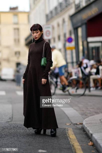 Mademoiselle Yulia wears pearl earrings, a brown wool turtleneck dress, a green bag, outside Beautiful People, during Paris Fashion Week - Womenswear...