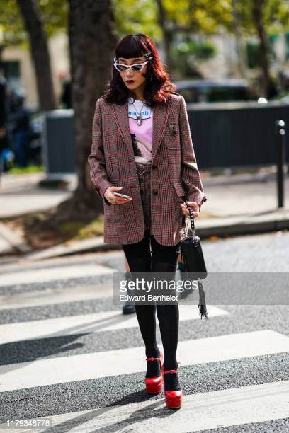 Mademoiselle Yulia wears sunglasses a checkered pattern blazer jacket a necklace a tshirt a mini skirt black tights red shoes a bag with attached...