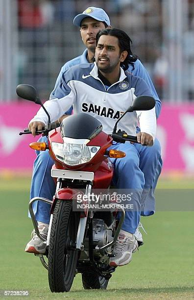 Indian cricketer Mahender Singh Dhoni and teammate Yuvraj Singh ride the manofthematch prizea motorbike awarded to Yuvraj after the third oneday...