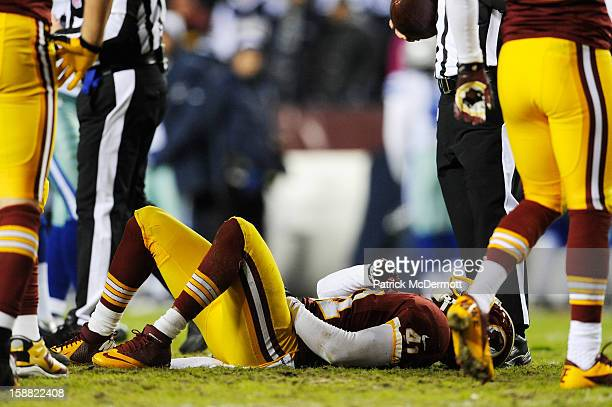 Madieu Williams of the Washington Redskins lays on the field after he was injured on the play against the Dallas Cowboys in the second quarter at...