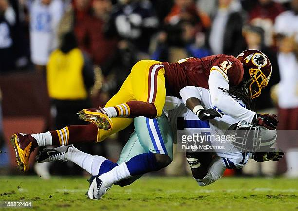 Madieu Williams of the Washington Redskins tackles Dwayne Harris of the Dallas Cowboys after a pass reception in the second quarter at FedExField on...