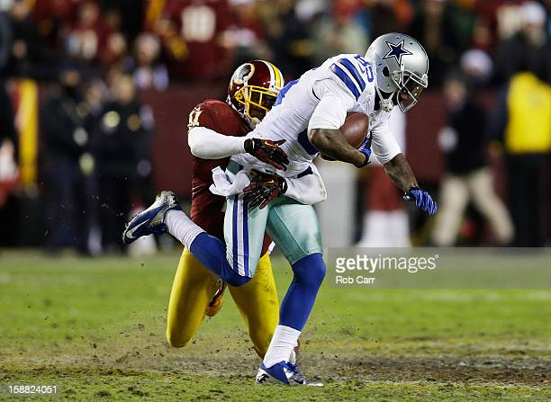 Madieu Williams of the Washington Redskins tackles Kevin Ogletree of the Dallas Cowboys after Ogletree caught a fourth quarter pass at FedExField on...