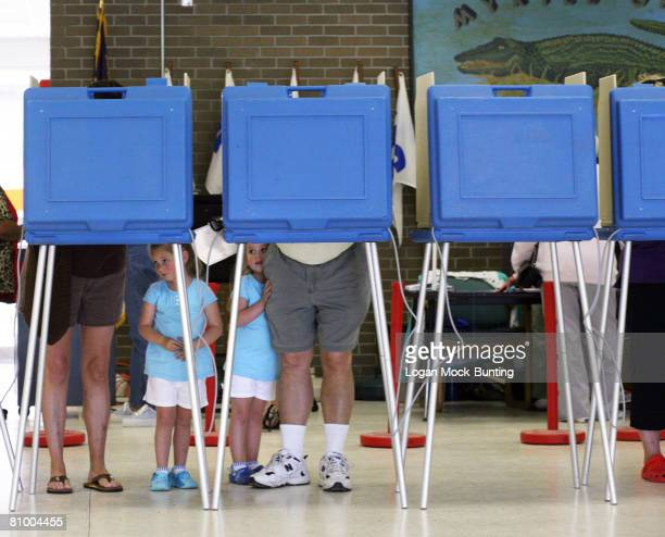 Madison and Payton Baize wait as their parents Jackie and Robbie Baize fill out ballots at the polling station at Myrtle Grove Middle school on May 6...