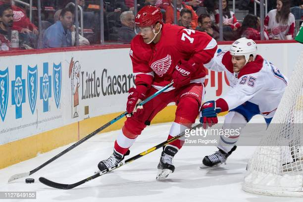 Madison Bowey of the Detroit Red Wings skates behind the net with the puck followed by Andrew Shaw of the Montreal Canadiens during an NHL game at...