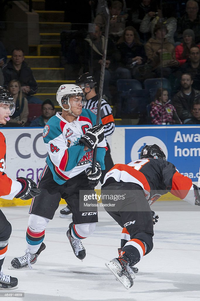 Madison Bowey #4 of the Kelowna Rockets checks Curtis Valk #18 of the Medicine Hat Tigers on January 24, 2014 at Prospera Place in Kelowna, British Columbia, Canada.