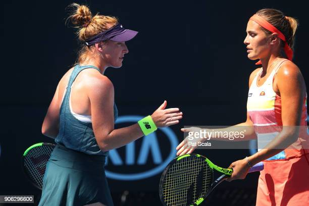 Madison Brengle of the United States and Monica Puig of Puerto Rico talk tactics in their first round women's doubles match against Alison Bai of...